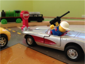 Image: teen playmobil figure driving car with mobile phone in hand